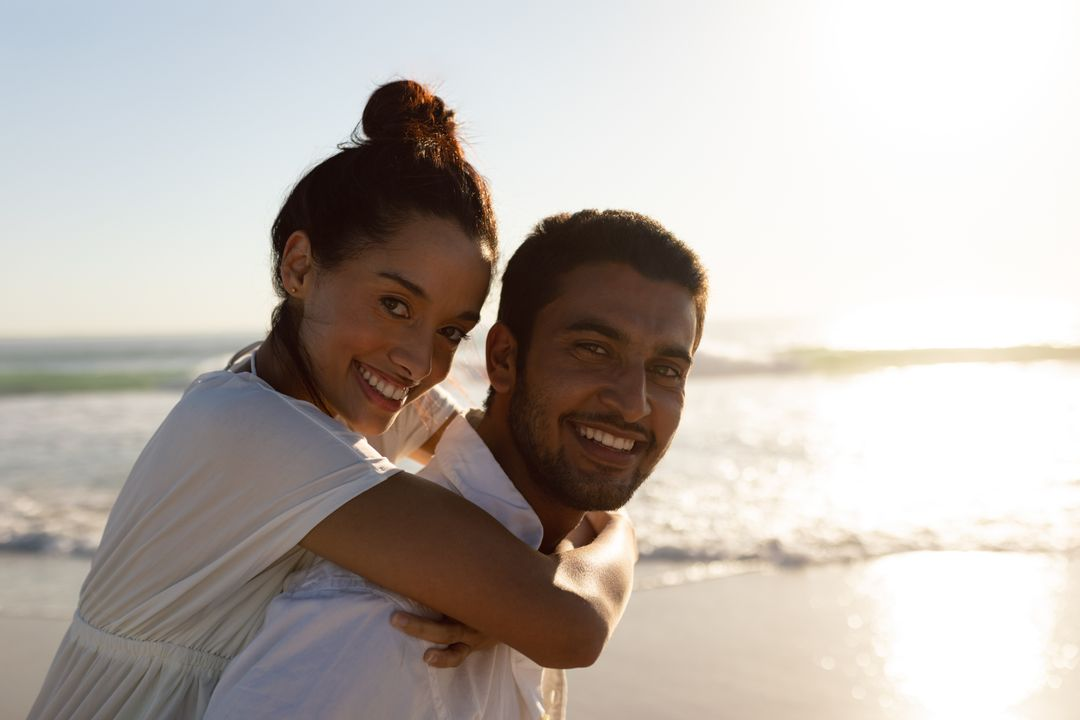 Portrait of man giving piggyback ride to woman on the beach