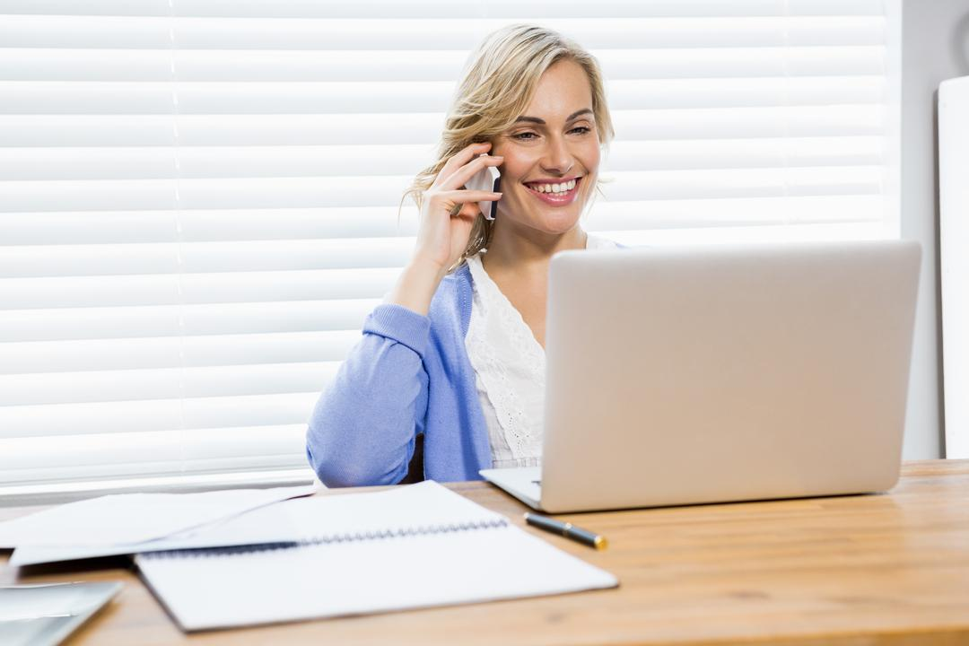 Beautiful woman talking on mobile phone while using laptop at home Free Stock Images from PikWizard