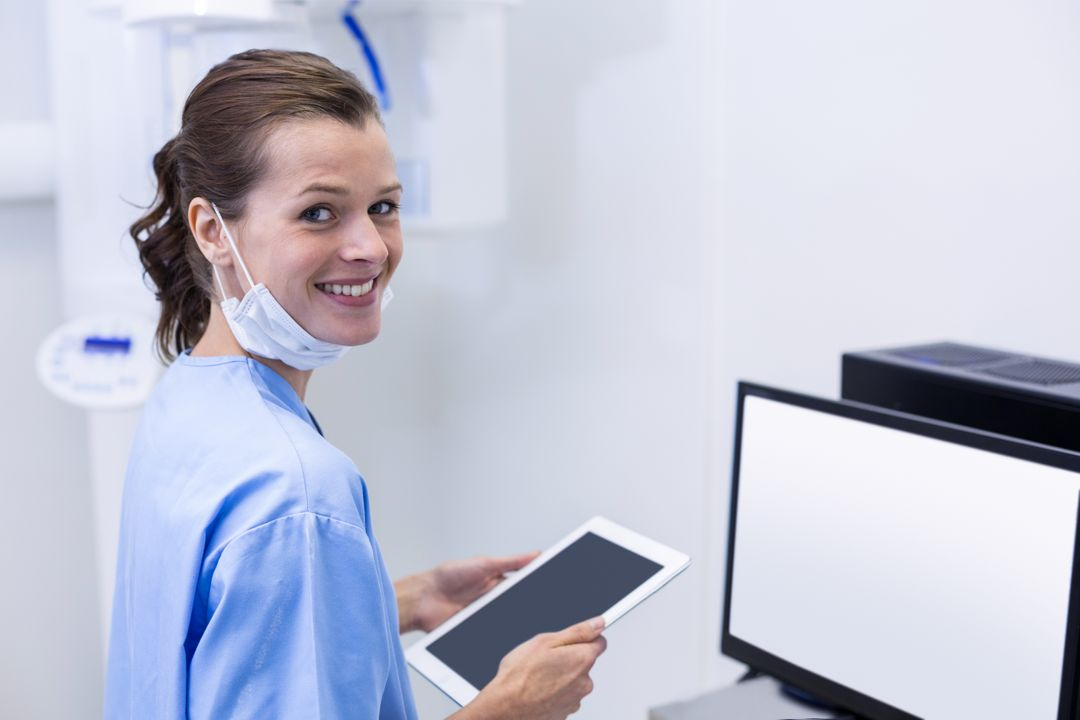 Portrait of smiling dental assistant holding digital tablet in dental clinic Free Stock Images from PikWizard