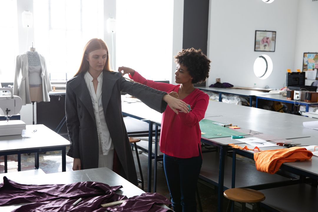 Front view of a young mixed race female fashion student measuring a jacket worn by a young Caucasian female student with long red hair, in a studio at fashion college Free Stock Images from PikWizard