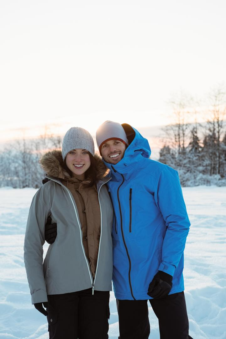 Portrait of smiling couple standing on snowy landscape