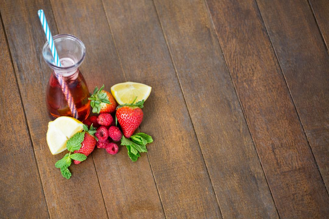 Bottle with berry cocktail and berry fruits on wooden board