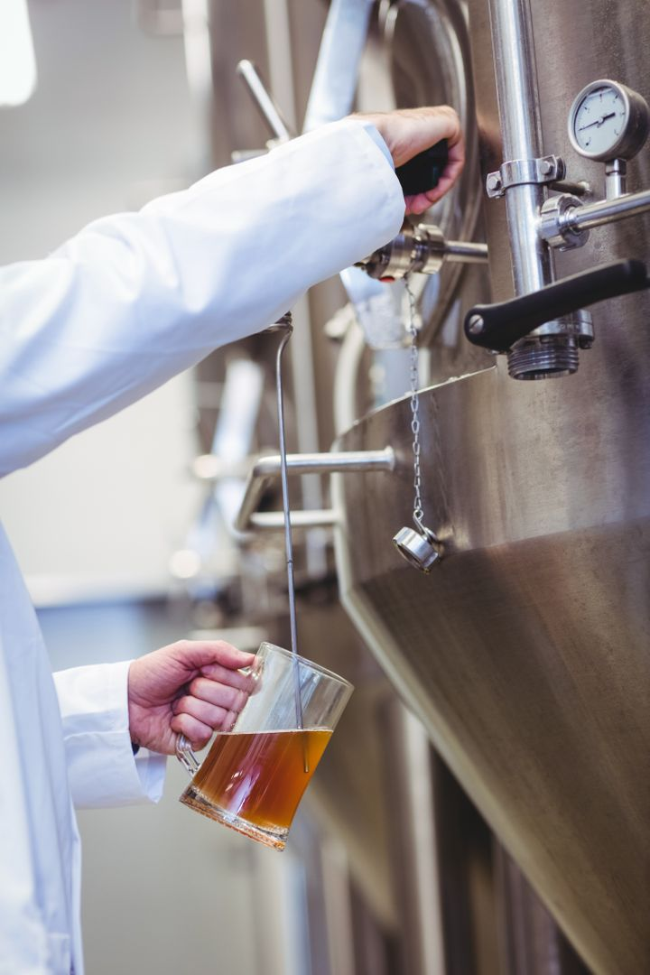 Cropped image of manufacturer filling beer into glass at brewery Free Stock Images from PikWizard