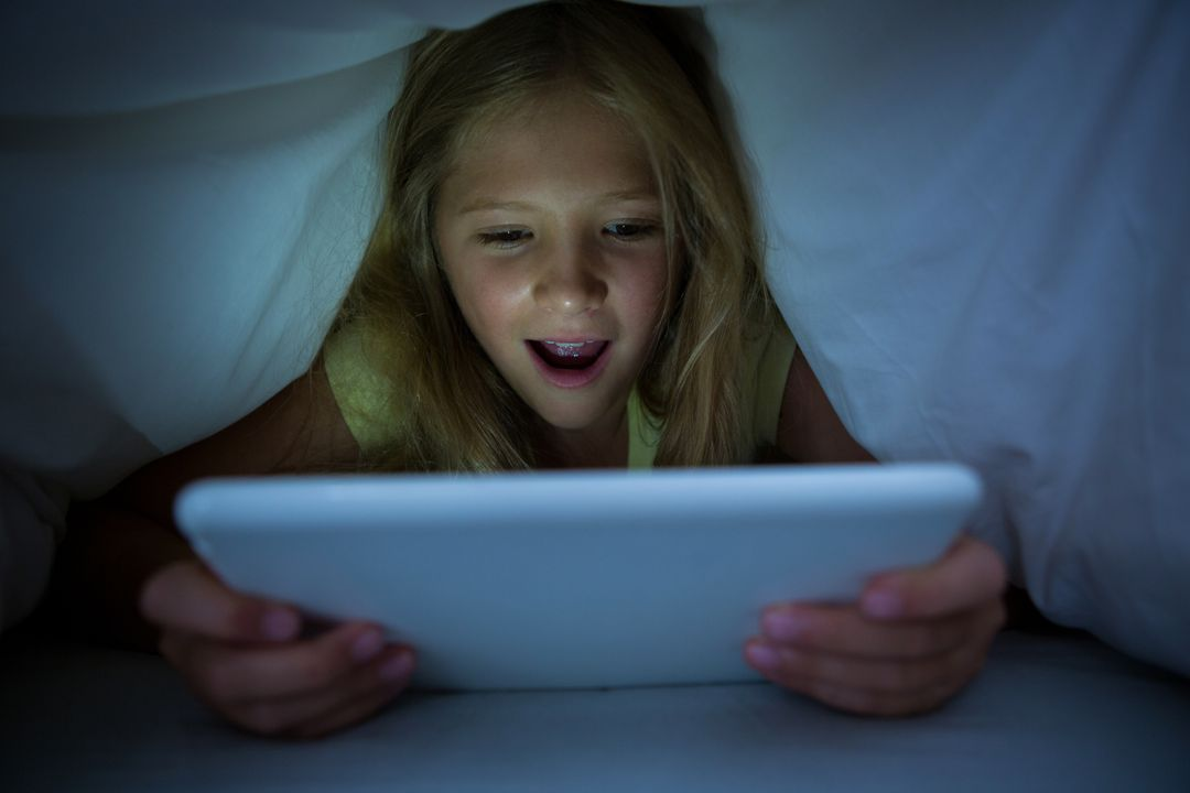 Happy girl using tablet computer while lying in bed with blanket on head Free Stock Images from PikWizard