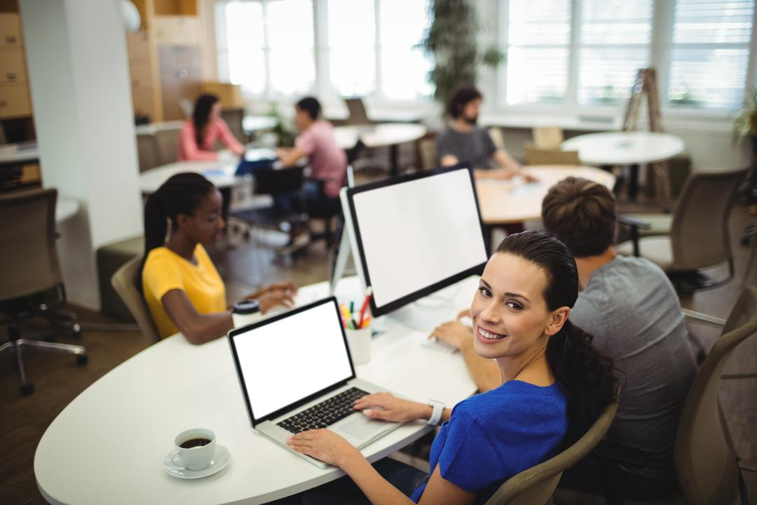 Portrait of woman using laptop at her desk in the office