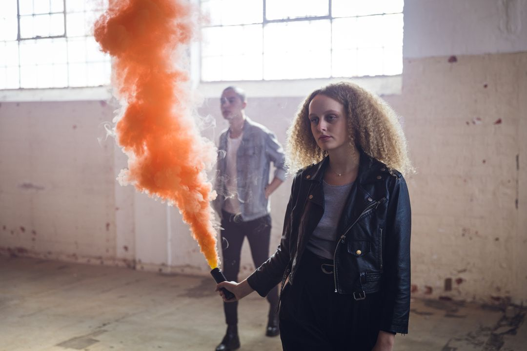 Front view of a hip young mixed race man and a hip young Caucasian woman in an empty warehouse, the woman holding a hand grenade, with orange smoke. Free Stock Images from PikWizard