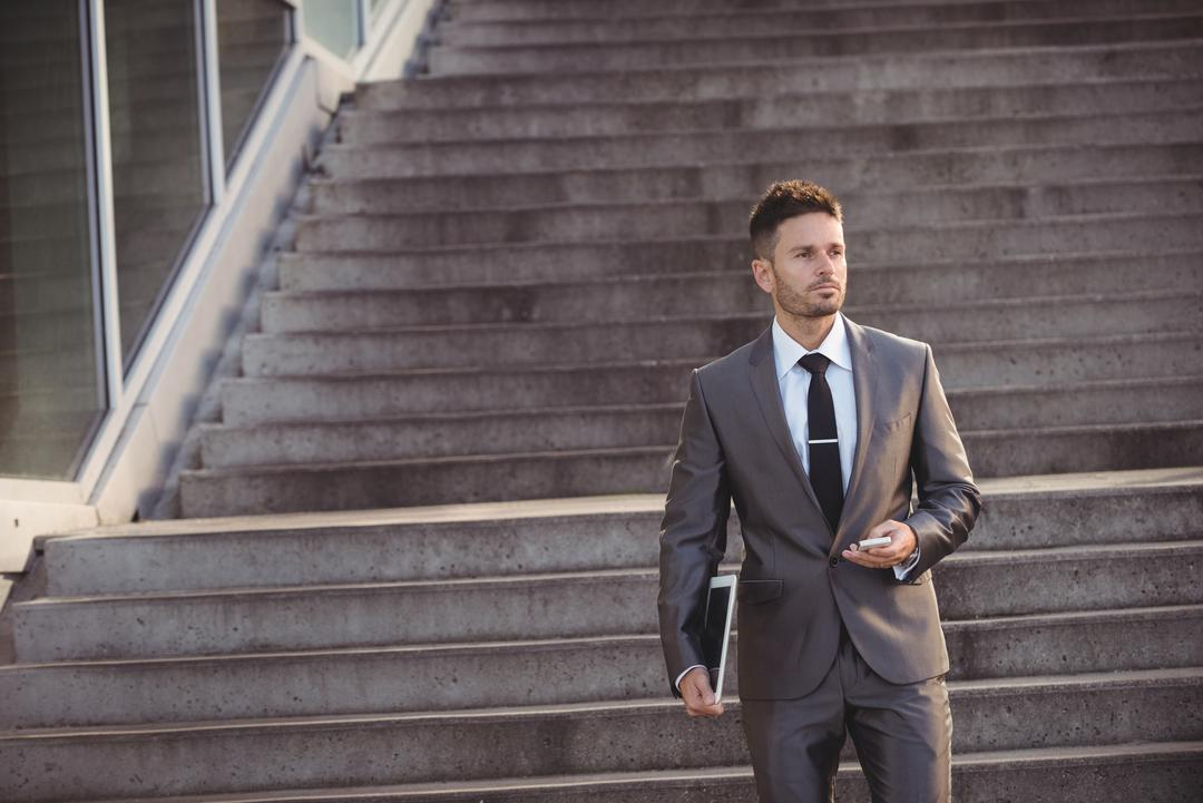 Businessman holding mobile phone while walking down steps Free Stock Images from PikWizard
