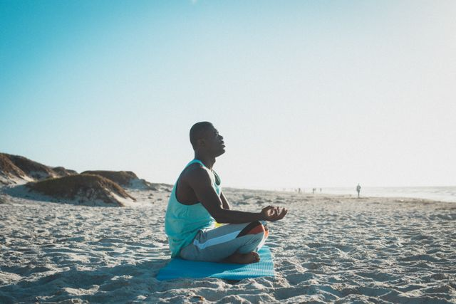 African american man exercising, practicing yoga, meditating on beach at sunset