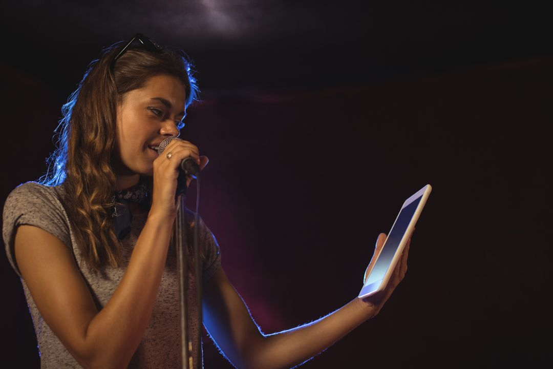 Singer speaking into a mic while holding a tablet