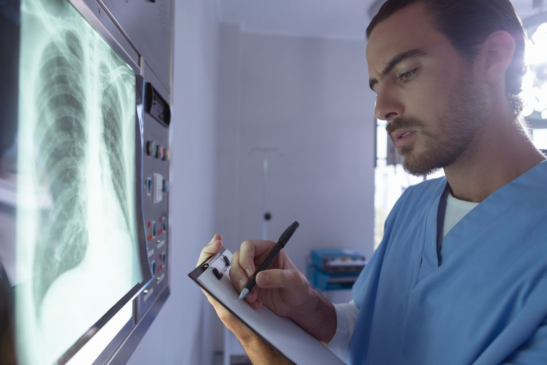 Male surgeon writing on clipboard while examining x-ray on x-ray light box in operation room at hospital
