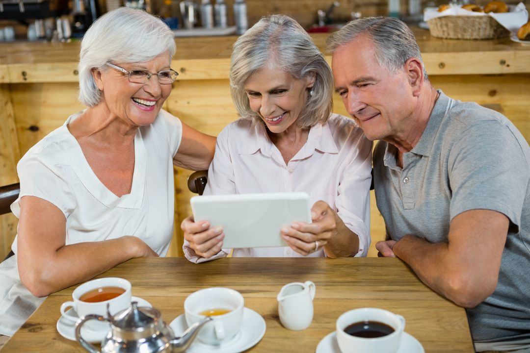 Group of senior friends using digital tablet in café Free Stock Images from PikWizard