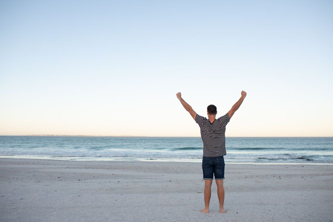 Rear view of man standing with arms outstretched on the beach