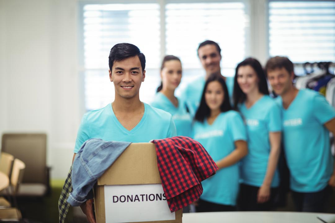 Volunteer holding clothes in donation box