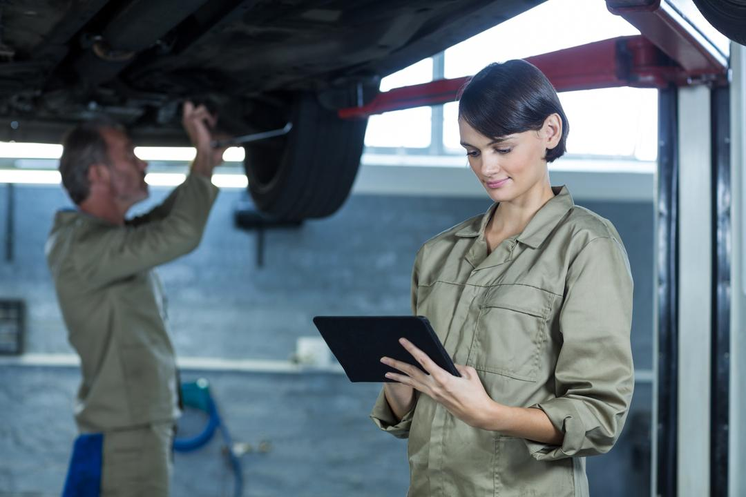 Female mechanic using digital tablet in repair shop