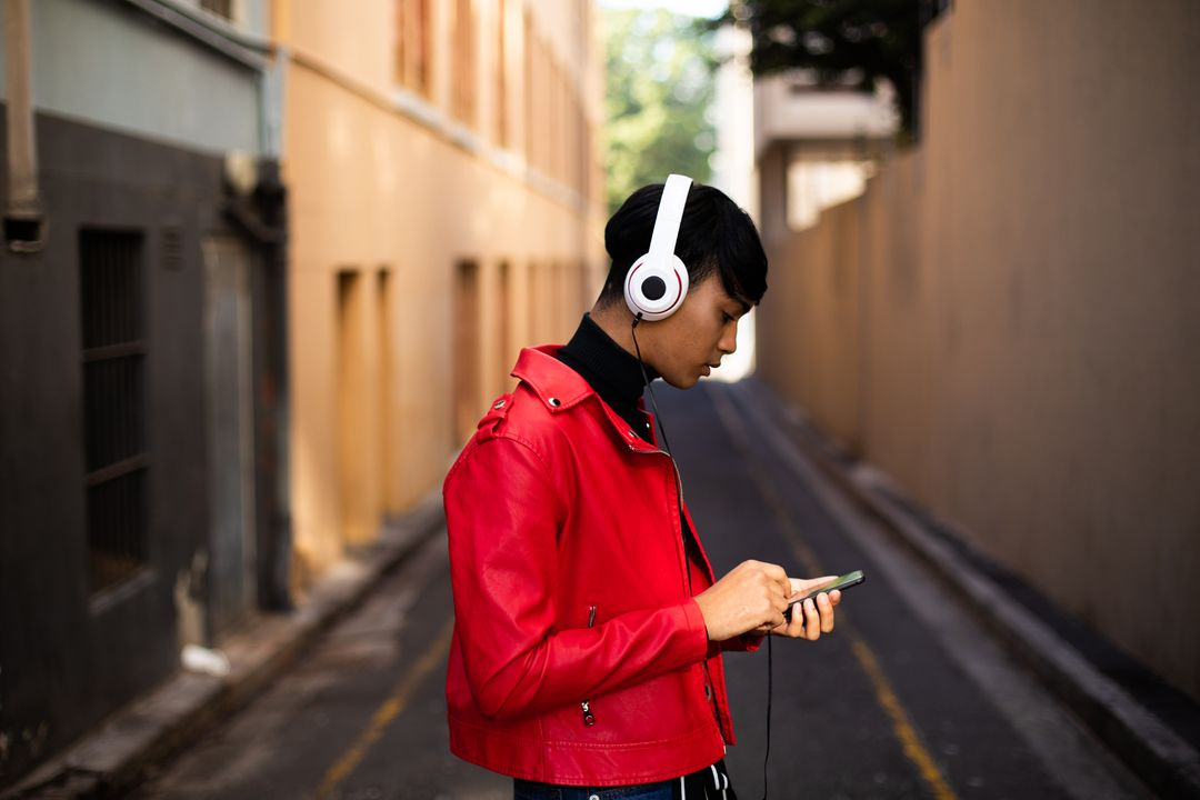 Side view of a fashionable mixed race transgender in the street, walking on the streets, listening to music on headphones, using smartphone
