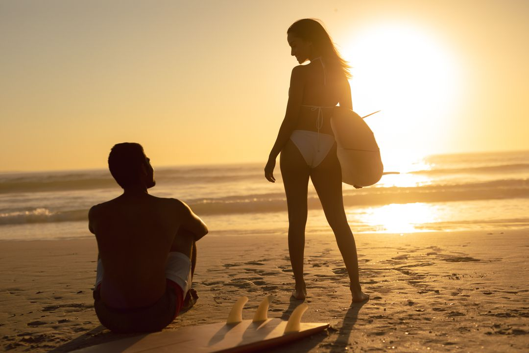 Rear view of couple interacting with each other on the beach during sunset