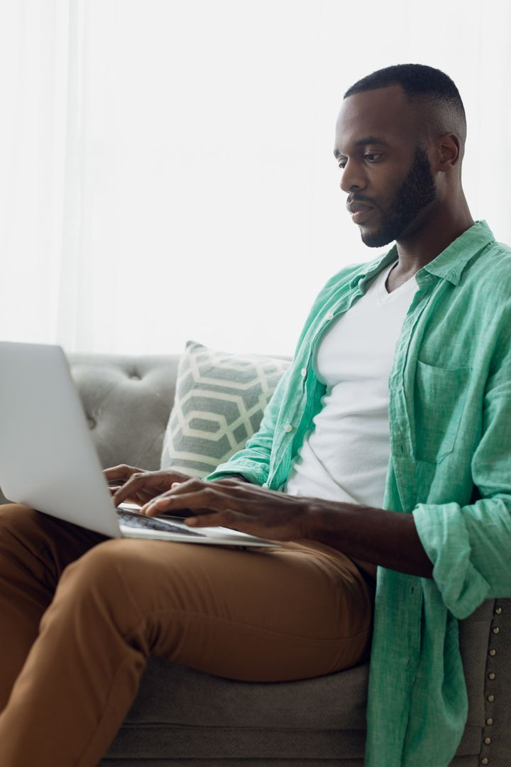 Side view of an African-American man sitting on a grey couch with white curtains inside a room while using a laptop Free Stock Images from PikWizard