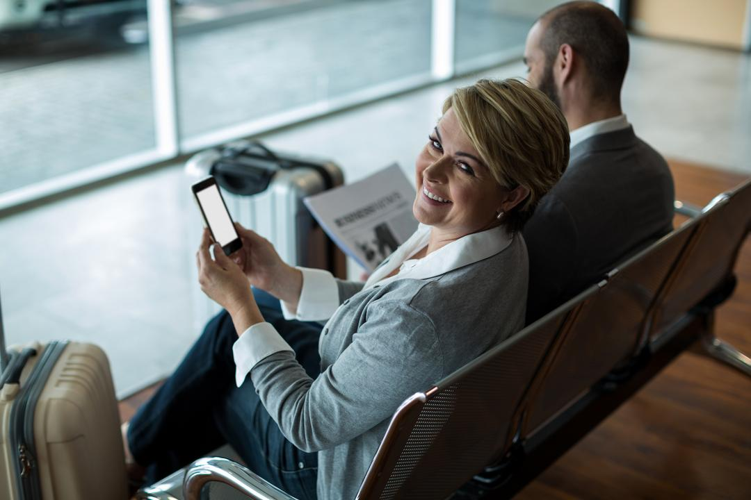 Portrait of smiling businesswoman with mobile phone sitting in waiting area at airport terminal Free Stock Images from PikWizard