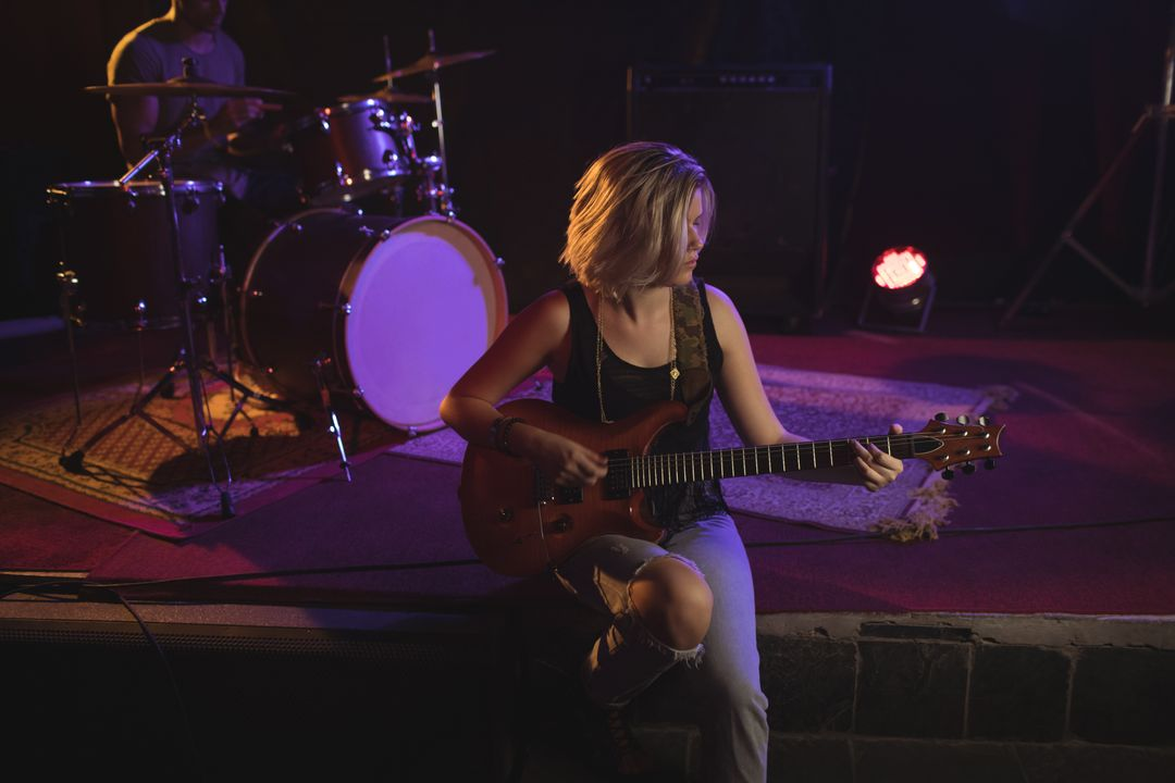 Female guitarist practicing while sitting on stage in nightclub Free Stock Images from PikWizard