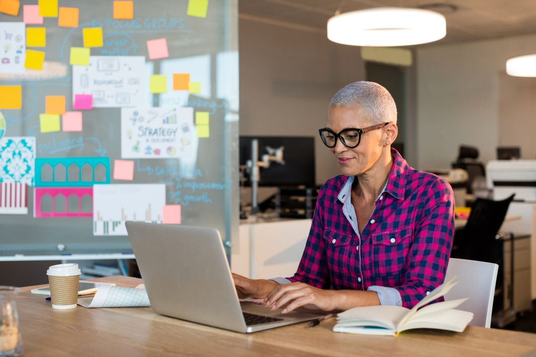 Creative businesswoman smiling while working on her laptop with a board of notes and ideas behind her