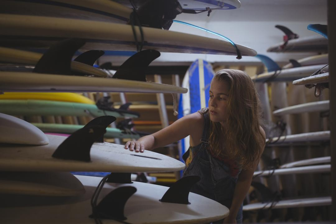 Woman selecting a surfboard in beach cabin Free Stock Images from PikWizard