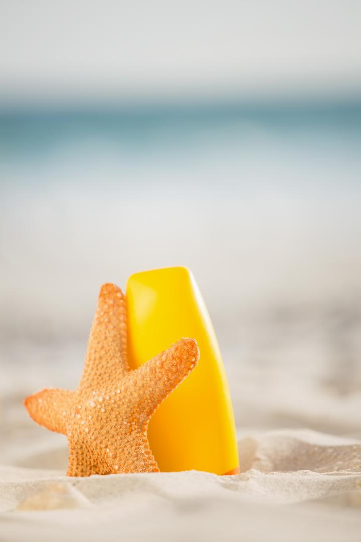 Bottle of sunscreen lotion and starfish kept on sand at beach