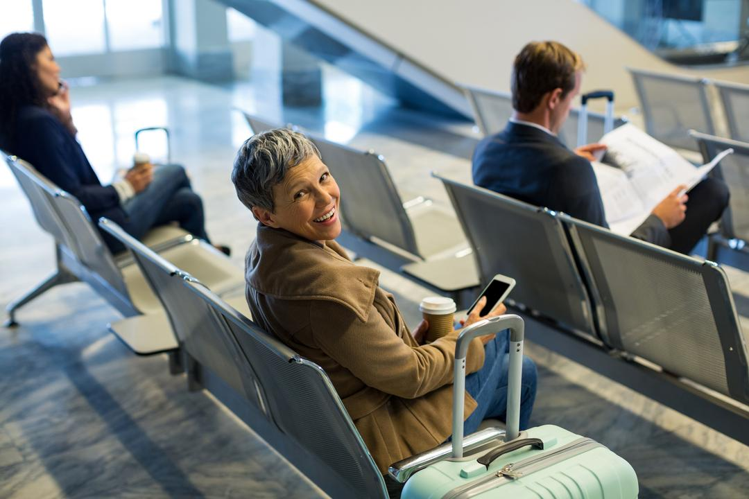 Commuter with coffee cup using mobile phone in waiting area at airport