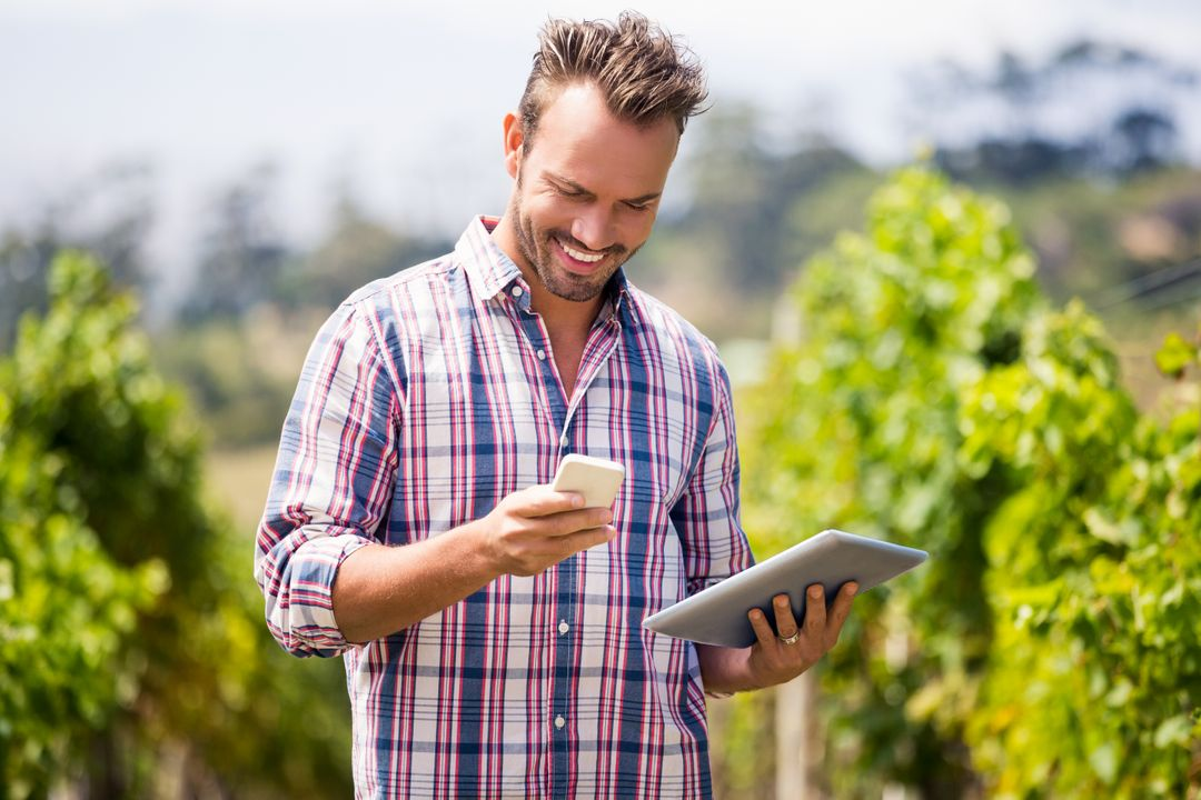 Young man with digital tablet using mobile phone at vineyard on sunny day