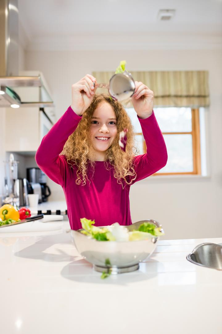 Girl holding lettuce in spoon at kitchen
