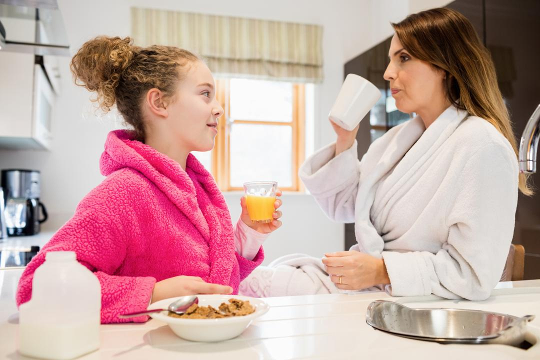 Mother and daughter having breakfast in kitchen at home