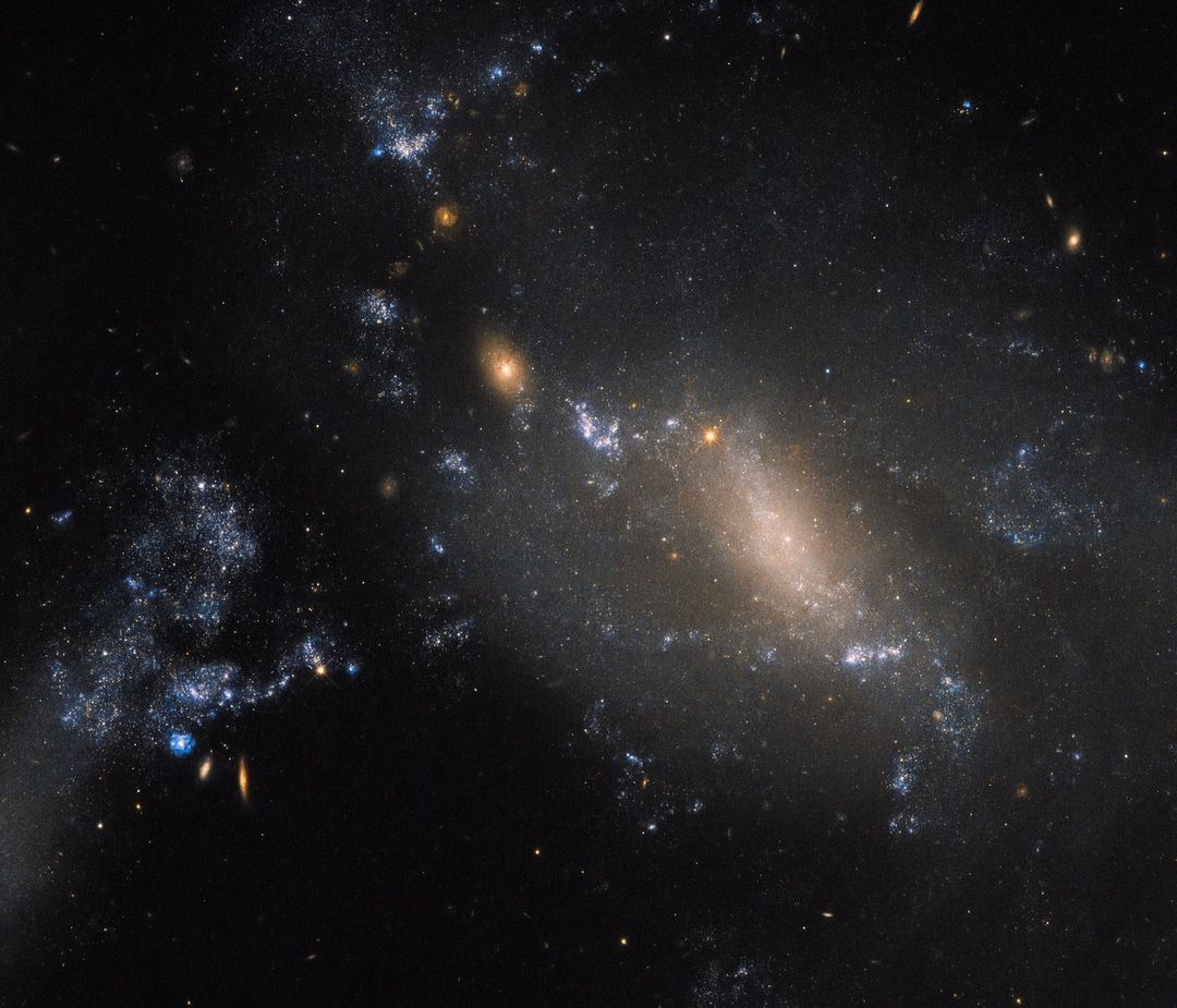 "Two galaxies in a cosmic dance defy conventions.   60 million light-years away in the constellation of Leo, the more diffuse and patchy blue glow covering the right side of the frame is known as NGC 3447B, while the smaller clump to the upper left is NGC 3447A.  Known together as NGC 3447, we're unsure what each looked like before they began to tear one another apart. So close that they are strongly influenced and distorted by the gravitational forces between them, the galaxies to twist themselves into the unusual and unique shapes seen here. NGC 3447A appears to display the remnants of a central bar structure and some disrupted spiral arms, both properties characteristic of certain spiral galaxies. Some identify NGC 3447B as a former spiral galaxy, while others categorize it as being an irregular galaxy.  Credit: NASA/Hubble  <b><a href=""http://www.nasa.gov/audience/formedia/features/MP_Photo_Guidelines.html"" rel=""nofollow"">NASA image use policy.</a></b>  <b><a href=""http://www.nasa.gov/centers/goddard/home/index.html"" rel=""nofollow"">NASA Goddard Space Flight Center</a></b> enables NASA's mission through four scientific endeavors: Earth Science, Heliophysics, Solar System Exploration, and Astrophysics. Goddard plays a leading role in NASA's accomplishments by contributing compelling scientific knowledge to advance the Agency's mission.  <b>Follow us on <a href=""http://twitter.com/NASAGoddardPix"" rel=""nofollow"">Twitter</a></b>  <b>Like us on <a href=""http://www.facebook.com/pages/Greenbelt-MD/NASA-Goddard/395013845897?ref=tsd"" rel=""nofollow"">Facebook</a></b>  <b>Find us on <a href=""http://instagrid.me/nasagoddard/?vm=grid"" rel=""nofollow"">Instagram</a></b>"