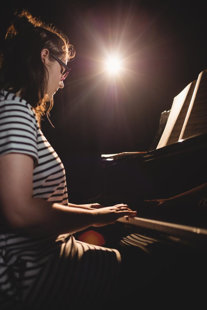 Female student playing piano in a studio