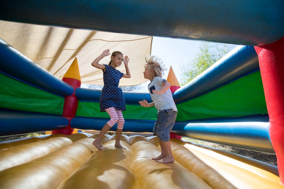 Full length of happy siblings jumping on bouncy castle at playground Free Stock Images from PikWizard