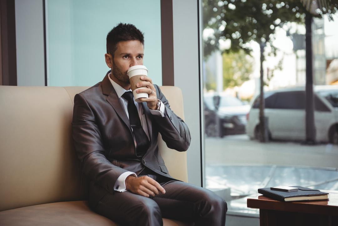 Businessman having coffee while sitting on sofa in the office