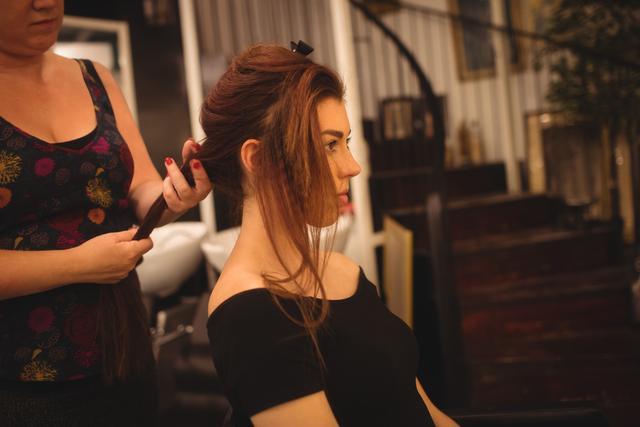 Beautiful woman styling her hair at saloon
