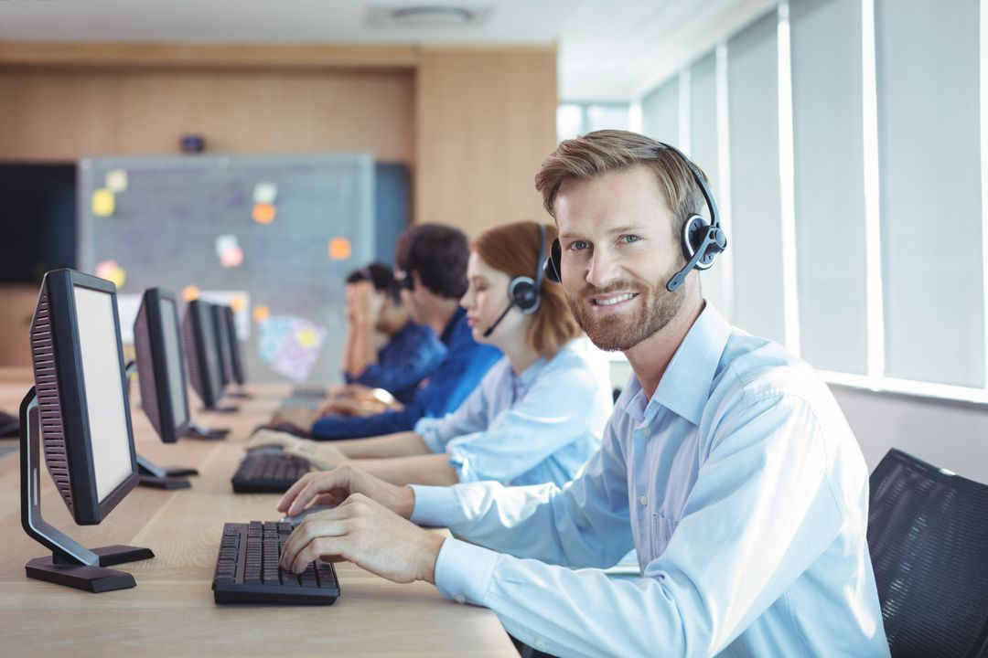 Portrait of smiling businessman working at desk in call center Free Stock Images from PikWizard