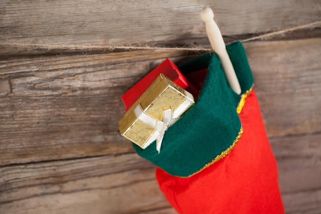 Christmas stocking with present box hanging against wooden wall during christmas time Free Stock Images from PikWizard