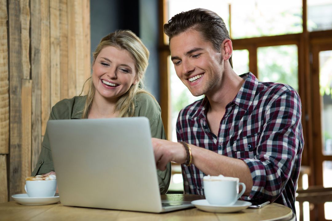 Cheerful young couple using laptop at table in coffee shop Free Stock Images from PikWizard