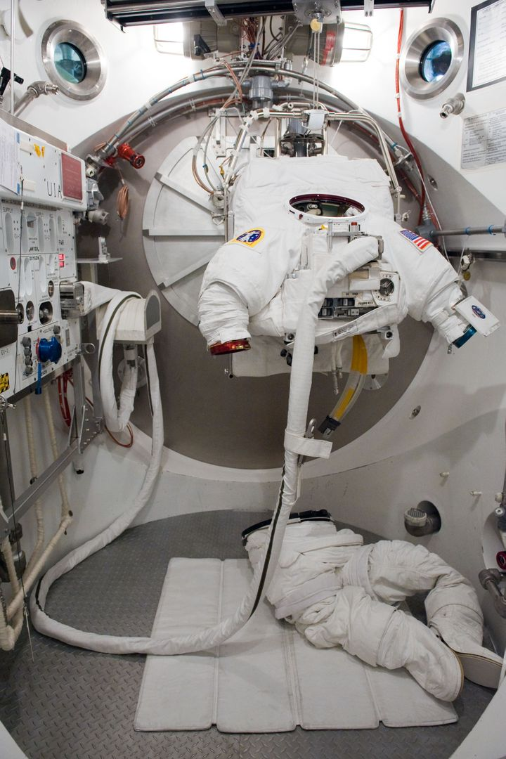 JSC2009-E-240471 (5 Nov. 2009) --- An empty Extravehicular Mobility Unit (EMU) spacesuit is photographed prior to a fit check with astronaut Clayton Anderson (out of frame), STS-131 mission specialist, in the Space Station Airlock Test Article (SSATA) in the Crew Systems Laboratory at NASA's Johnson Space Center.