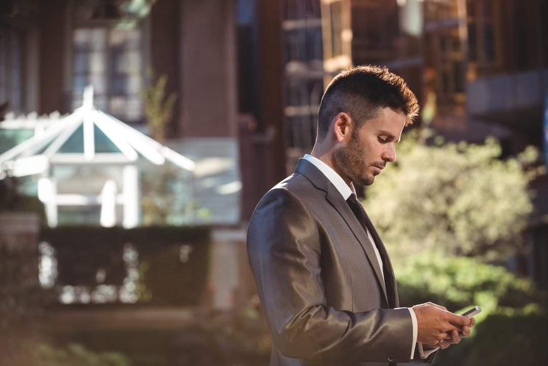 Businessman using mobile phone near office building Free Stock Images from PikWizard