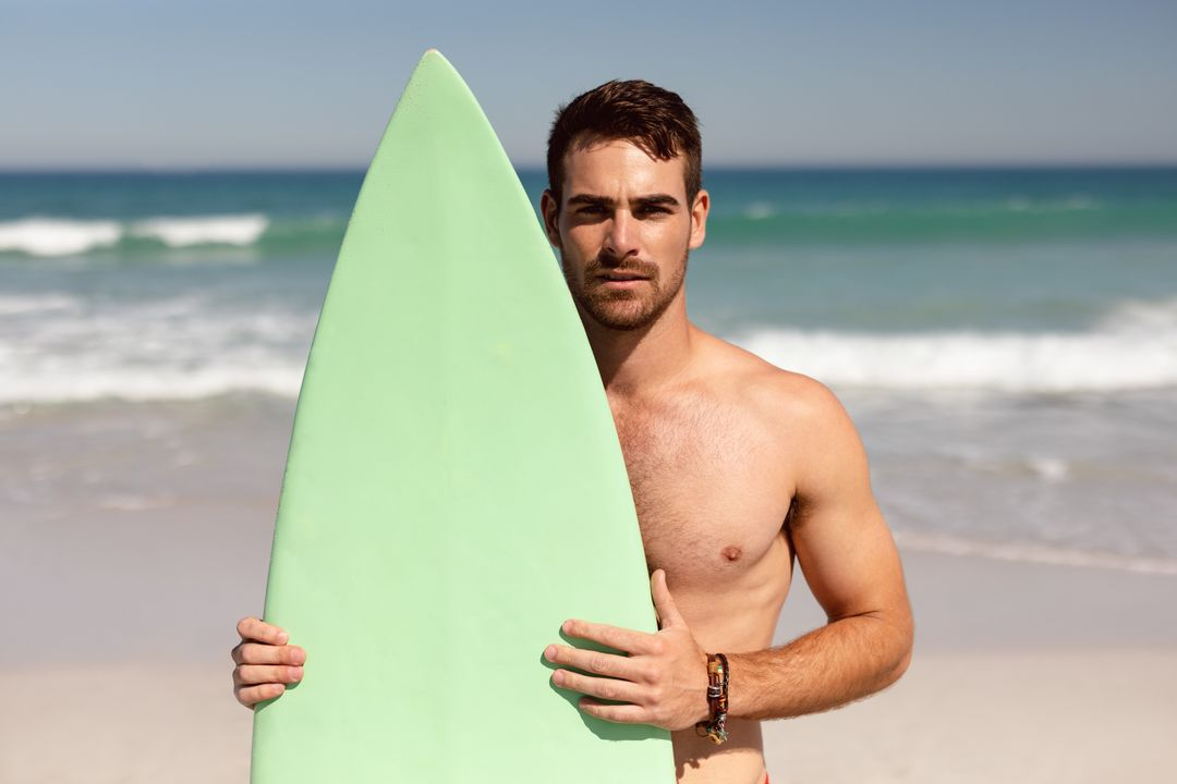 Front view of shirtless young Caucasian man with surfboard looking at camera on beach in the sunshine