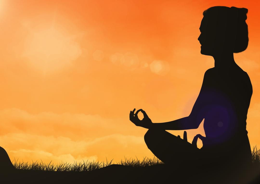 Silhouette of woman sitting for meditation on grass against orange sky