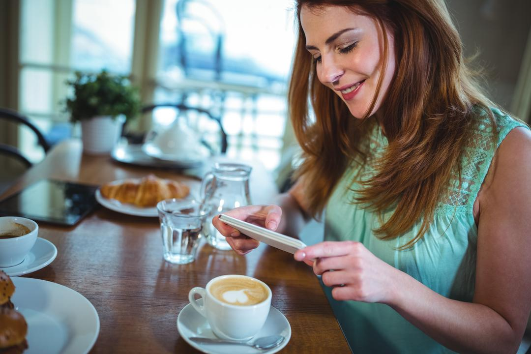 Smiling woman clicking photo of coffee from mobile phone in café