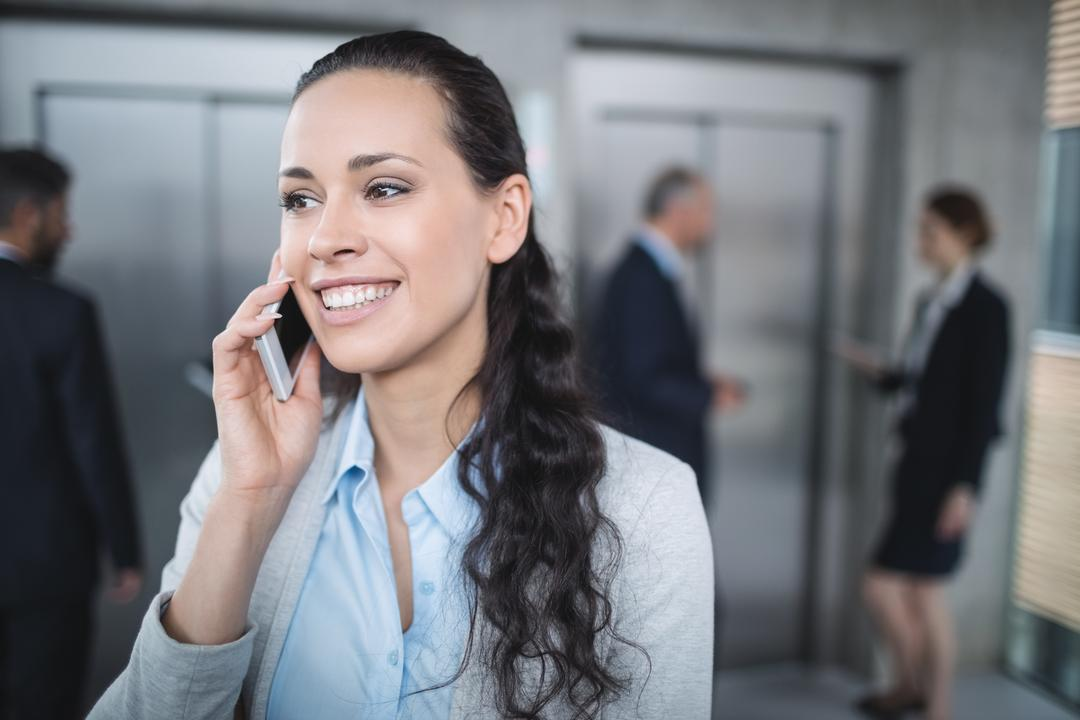 Businesswoman talking on mobile phone in office Free Stock Images from PikWizard