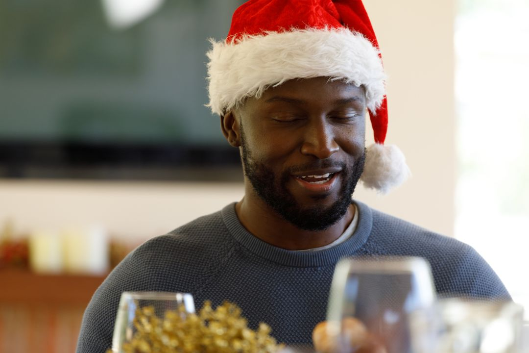 Front view of an african-american man wearing a santa hat while sitting at the christmas dinner table. Wine glasses can be seen in the foreground. Free Stock Images from PikWizard