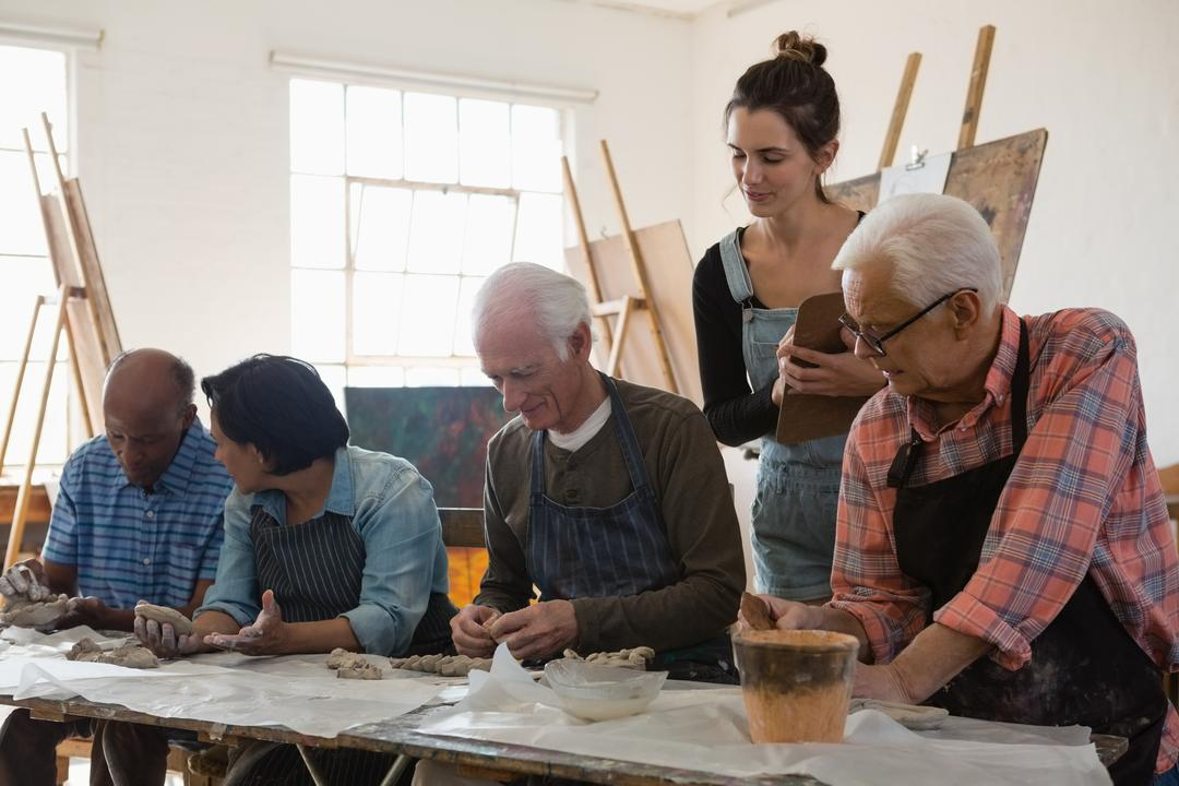 Woman examining senior people making clay product at table in art class