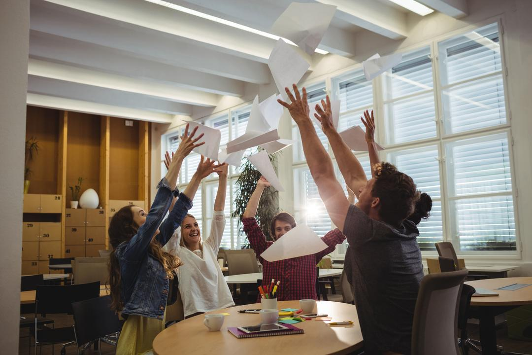 Group of excited business executives throwing paper and having fun in office