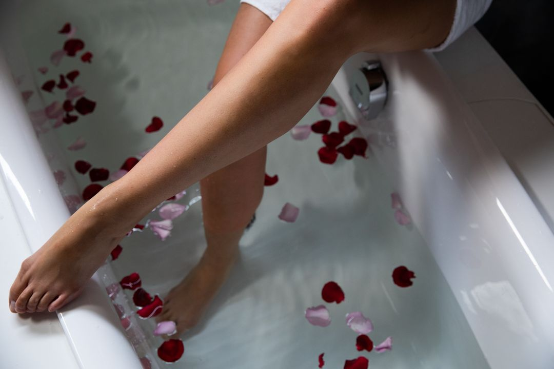 Close up the legs of a young Caucasian woman, with one foot in the water with rose petals on the side, while she sits on the side of the bathtub Free Stock Images from PikWizard
