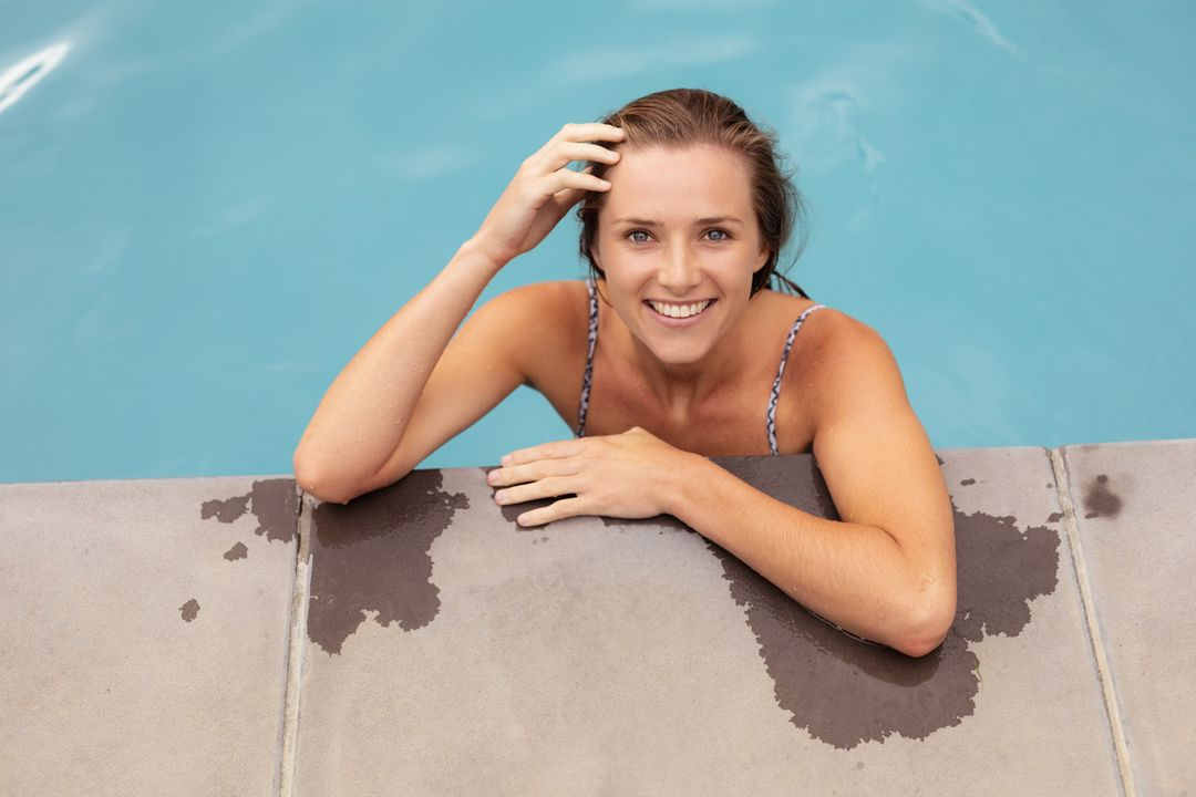 Portrait of woman standing at the edge of swimming pool