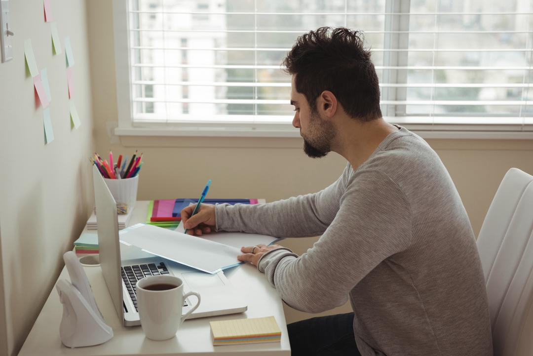 Attentive man writing on document while sitting at desk